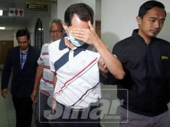 Kok Yeow (belakang) dibawa keluar dari mahkamah selepas prosiding kes.