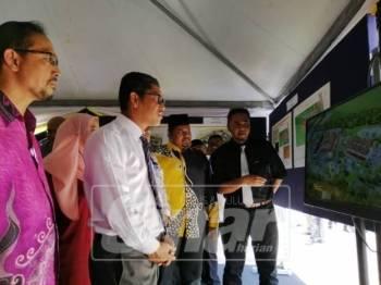Ahmad Faizal (dua, kiri) mendengar penerangan mengenai projek pembangunan SMTDR daerah Kinta yang akan memulakan pembinaannya tahun hadapan.