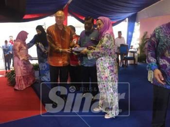 Raja Zarith menyerahkan sijil penghargaan kepada petugas dan NGO yang memberikan khidmat di Hospital Sultanah Aminah.