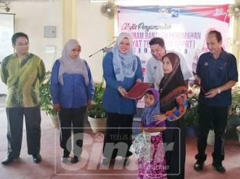 Rina diiringi Sazmi dan Iskandar Zurkarnain menyampaikan sijil bantuan perumahan rakyat termiskin kepada penerima di sini, hari ini.