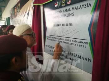 Abdul Hadi menandatangani plak pusat operasi Unit Amal Pas Baling.