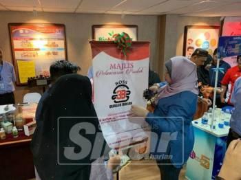 Rina memotong riben pelancaran produk Burger Bakar ketika lawatan ke KIM di Pengkalan Chepa, hari ini.