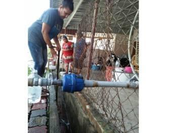Salah seorang penduduk mengambil air di hadapan rumah seorang peniaga di Taman Minang hari ini. - Foto Bernama