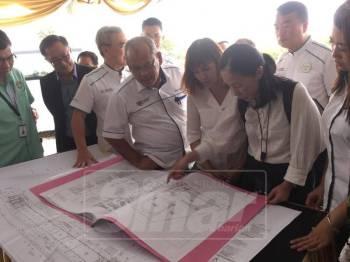 Nie Ching (tengah) melihat pelan SJKC Ladang Grisek yang sedang menjalani proses pembinaan.