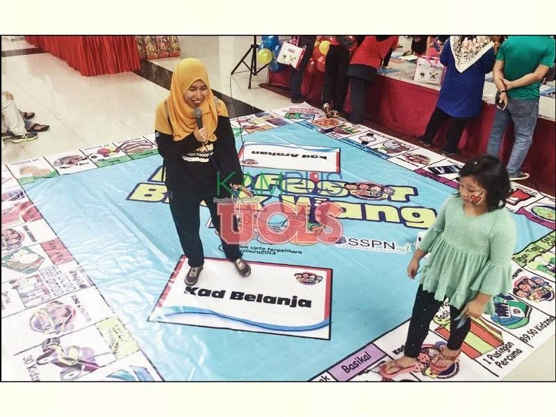 Petugas PTPTN ketika membantu para peserta yang bermain dalam permainan Profesor Bijak Wang.