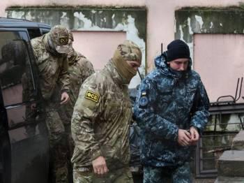 Salah seorang kelasi Ukraine yang ditahan diringi ke mahkamah. - Foto AFP