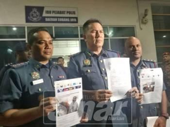 Azmi (dua, kanan) menunjukkan laporan polis yang dibuat.