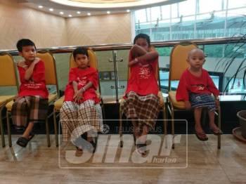Muhamad Isyraf (kanan) teruja sambil menunggu giliran dirinya untuk dikhatankan bersama rakan-rakan lain pada Program Khatan beramai-ramai di KPJ Pahang Specialist Hospital di sini.