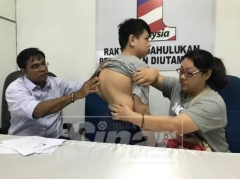 Karen dan Mohd Rawi menunjukkan keadaan tulang belakang Jasper Mark yang kelihatan membengkok dan memerlukan pembedahan segera, hari ini.
