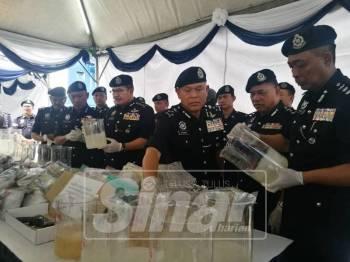 Mohamad (tiga, kanan) menunjukkan rampasan dadah serta peralatan memproses dalam serbuan di sekitar Lembah Klang, Selasa lalu.