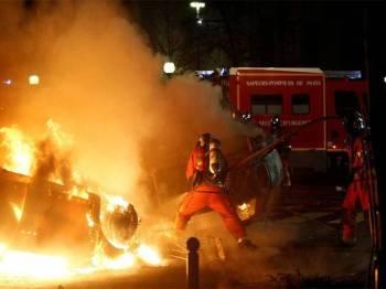 Anggota bomba memadam kenderaan yang dibakar perusuh 'ves kuning'. - Foto Reuters