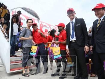 Ahmad Faizal menyambut salah seorang penumpang yang memulakan perkhidmatan pertama AirAsia Singapura-Ipoh di LTSAS, hari ini.