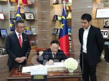 Adly (kanan) memerhatikan Liu Jie menandatangani buku pelawat ketika menerima kunjungan hormat delegasi Wilayah Sichuan di Seri Negeri, semalam.