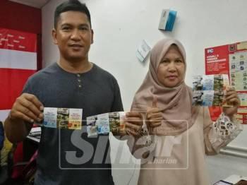 Norhayati bersama suaminya, Mohd Henyzam menebus tiket percuma ke taman tema di Bukit Gambang Resort City di Pejabat Sinar Harian semalam.