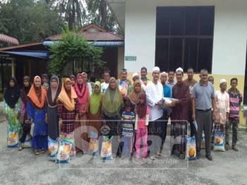 Ahmad Zulkifli (lapan, kanan) menyerahkan sumbangan beras kepada penoreh getah di Keda Bukit Kura, Kuala Nerang.