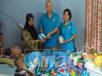 Hamiza Suriati (kiri) menerima sumbangan bekalan susu untuk Mohamad Amirul yang disumbangkan oleh Kelab Kebajikan Cakna Kelantan.