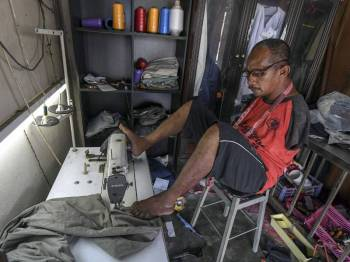 Pok Su Mie sedang menyiapkan pakaian yang dipesan oleh pelanggan di kedai jahitnya yang terletak di Pulai Chondong di sini.  - Foto Bernama