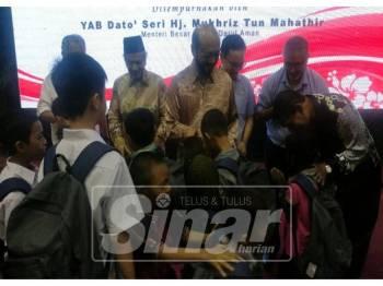 Penerima sumbangan tidak melepaskan peluang bersalam-salaman dengan Mukhriz (tengah).