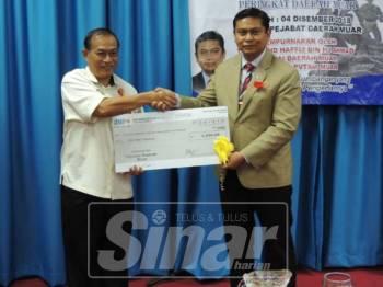 Samsudin (kiri) menerima replika cek daripada Mohd Haffiz bernilai RM5,000 bagi sumbangan untuk Tabung Pahlawan Peringkat Daerah Muar.