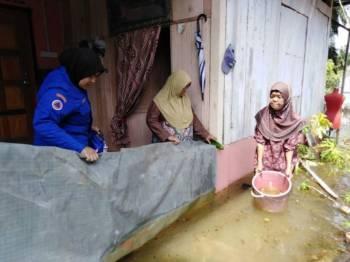 Anggota sukarelawan APM meninjau keadaan banjir di Lorong Pisang, Kampung Asahan yang masih belum surut. -  Foto ihsan APM