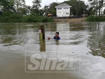 Seorang penduduk menunjukkan paras air di Sungai Golok sudah berada pada paras amaran iaitu 8.73.
