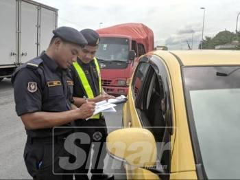 Anggota JPJ Selangor melakukan pemeriksaan ke atas kenderaan semasa operasi bersepadu dijalankan.