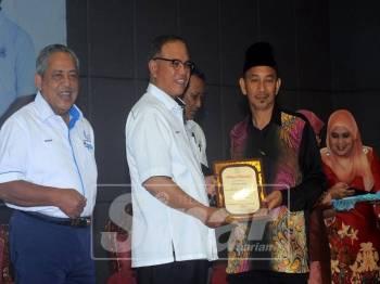 Wan Rosdy (dua, kiri) menyampaikan watikah pelantikan dalam majlis itu di Dewan Sultan Haji Ahmad Shah, Kuala Lipis, semalam.