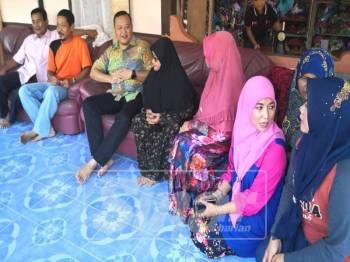 Rizam (tiga kiri) bersama sebahagian ahli Umno melawat rumah seorang penduduk pada Program Ziarah Kasih Dun Sungai Air Tawar.