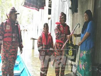 Suhaimi (dua,kanan) menyampaikan sumbangan makanan kepada salah seorang penduduk semasa program 'Door to Door' di Kampung Kubang Pak Itam.
