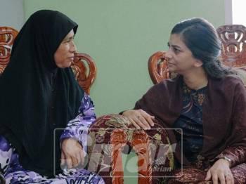 Che Puan Muda Zaheeda (kanan) bertanya khabar kepada Asma (kiri) ketika berkenan menziarahi keluarga itu.