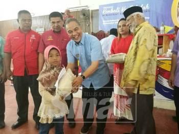 Amiruddin menyampaikan sumbangan kepada salah seorang murid.