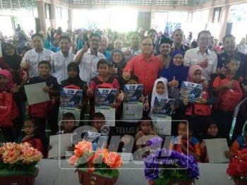 Wan Rosdy (merah, berdiri) bersama sebahagian penerima bantuan persekolahan TNB, di Dewan Orang Ramai Kuala Medang, hari ini.