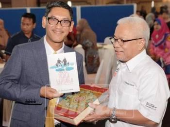 Ahmad Faizal (kiri) menerima cenderamata daripada Hussamuddin.