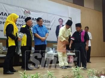 Mohd Anuar (empat, kiri) menyerahkan sumbangan kepada penerima terpilih dalam majlis tersebut.