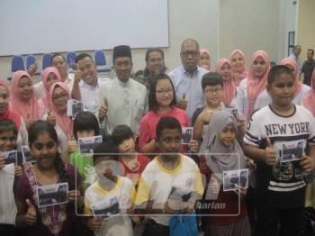 Ab Hamid diiringi Mohammad Fakhruddin merakamkan gambar bersama penerima bantuan pada program Majlis Bantuan Khas Persekolahan Menteri Besar Pahang di MTNP, di sini hari ini.