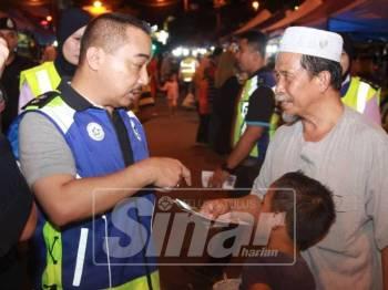 Suffian (kiri) sedang memberi penerangan tentang kesedaran jenayah kepada salah seorang pengunjung  KT Walk, Jalan Sultan Ismail, di sini, malam tadi.