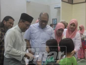 Mohammad Fakhruddin (kiri, depan) diiringi Ab Hamid menyampaikan bantuan persekolahan kepada murid-murid yang terpilih Majlis Bantuan Khas Persekolahan Menteri Besar Pahang di Dewan MTNP, semalam.