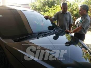 Yunos (kanan) bersama Mohd Kassim melihat kereta dibeli oleh Allahyarham Muhammad Adib yang mahu digunakan selepas berkahwin.