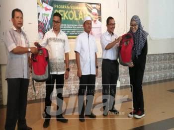 Dr Noor Azmi(dua kanan) turut berkesempatan menyerahkan sumbangan set kelengkapan sekolah kepada sebahagian pelajar memerlukan Dun Selinsing sambil diiringi Ahmad Saqif Ansorullah (tiga kiri).