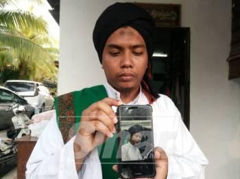 Mohd Firdaus menunjukkan gambar ayahnya yang disimpan dalam telefon bimbitnya.