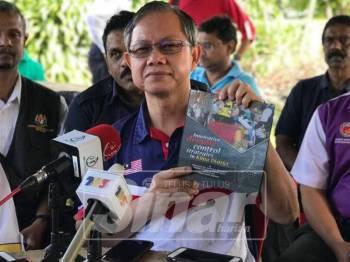 Boon Chye menunjukkan buku yang menunjukkan kaedah-kaedah pengawalan denggi yang berkesan di sekitar rumah selepas merasmikan program Gotong Royong dan Kesedaran Denggi di Kampung Rapat Jaya Tambahan, hari ini.