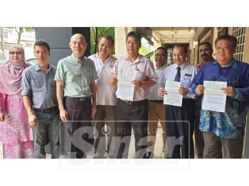 Lip Eng (tiga, kiri) bergambar bersama wakil pihak sekolah yang menerima bantuan tersebut.