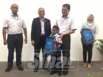 Shahrull Allam (dua, kanan) bersama Hassan (tiga, kanan) ketika menyampaikan sumbangan kepada salah seorang penerima pada program berkenaan.