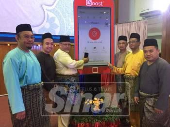 Aminolhuda (tiga, kiri) melakukan gimik perasmian mencuba sistem Boost untuk Tabung Pembangunan Masjid dan Amal Jariah Johor yang kini boleh digunakan atas talian.