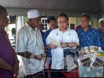 Abdul Fatah (empat, kanan) menunjukkan sijil koperasi milik Allahyarham Adib kepada Mohd Kassim.