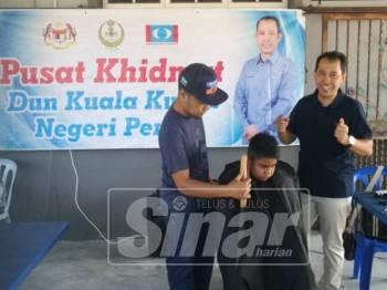 Abdul Yunus (kanan) menyantuni beberapa kanak-kanak yang mendapatkan khidmat gunting rambut percuma ditawarkan pihaknya di Pejabat Pusat Khidmat Adun Kuala Kurau di sini, hari ini.