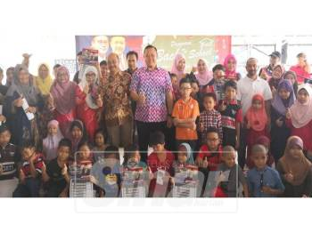 Rizam (berdiri tengah kanan) bersama kepimpinan Umno Bahagian Sabak Bernam pada Program Back to School di Pejabat Adun Sungai Air Tawar, di sini.