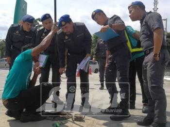 Azman  (tiga, kiri) bersama penguatkuasan KPDNHEP melakukan pemeriksaan bekalan bahan api di stesen minyak di R&R Ulu Bernam.