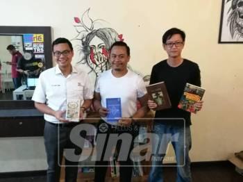 Chean Chung (kiri) bersama Shee Lim (kanan) dan Hariz menunjukkan buku yang disediakan di Gunteng Barbershop Indera Mahkota.