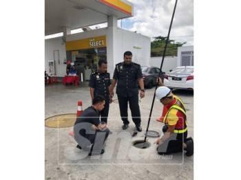 Sharizan (kanan berdiri) melakukan pemeriksaan bekalan petrol dan diesel di sebuah stesen minyak di Pontian.